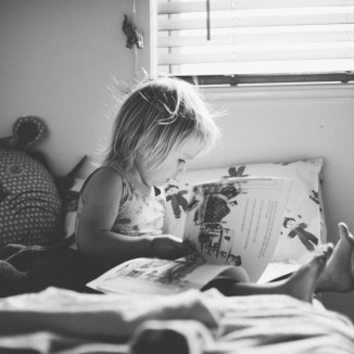 Black and white image of a blonde child reading on the bed
