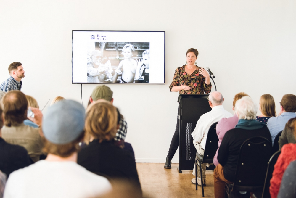 Colour image of Brisbane Photographer Briony Walker presenting a slideshow to a crowded room at CameraPro