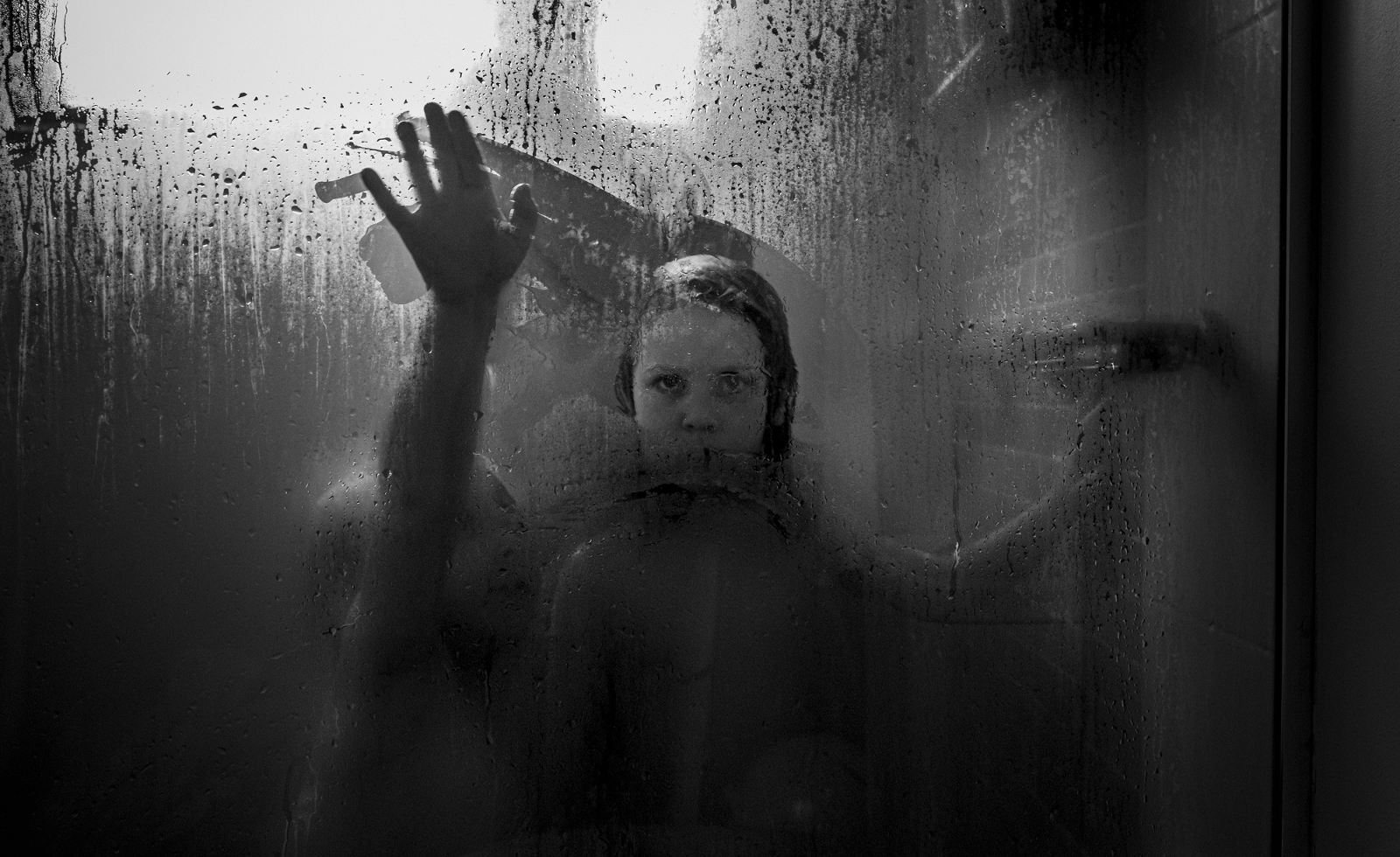 Black and white image of siblings writing on the shower glass