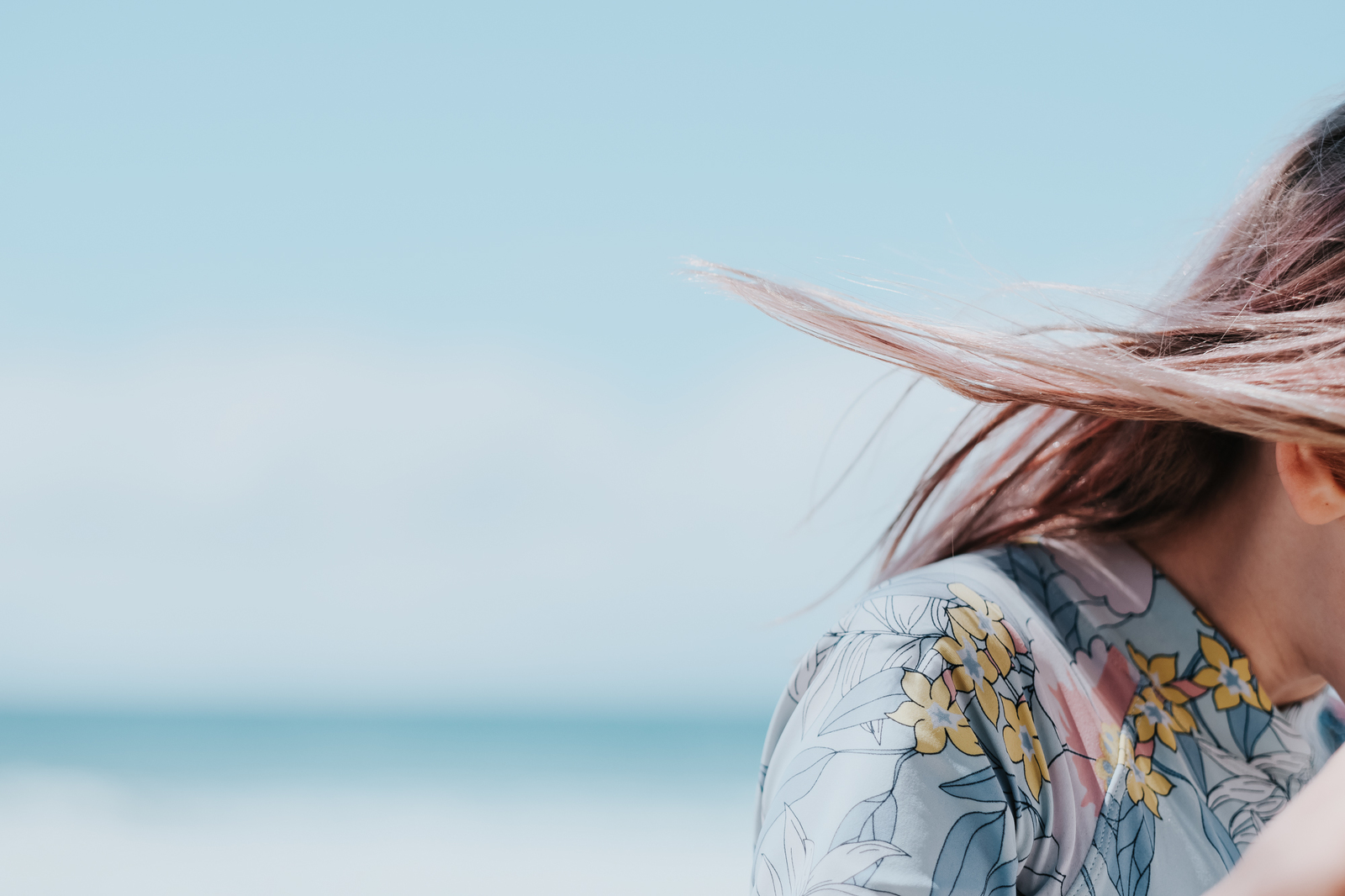 A young girl's pale pink hair against a backdrop of the ocean