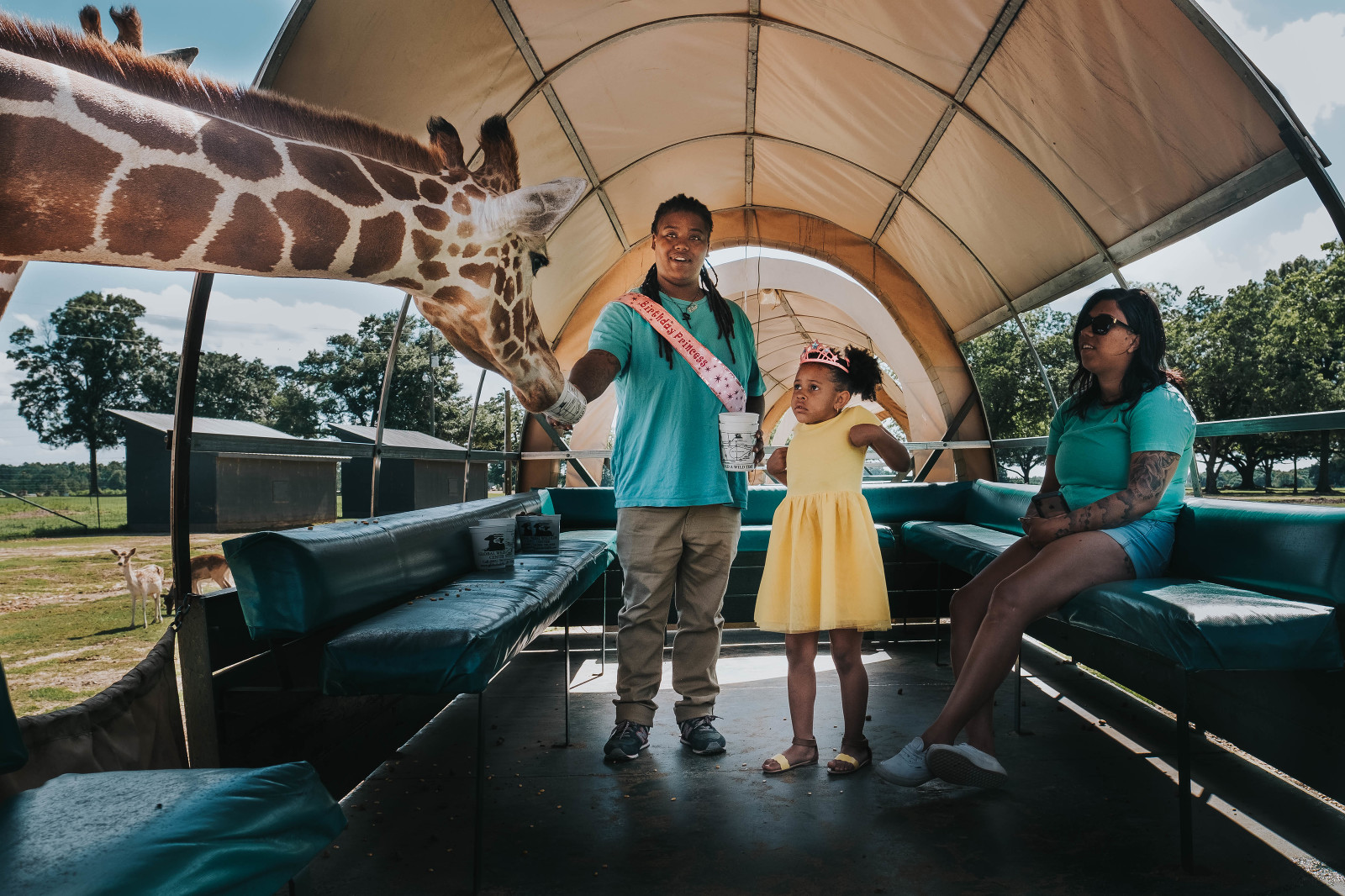 Same sex couple, women of colour with young child feeding giraffes at a safari park