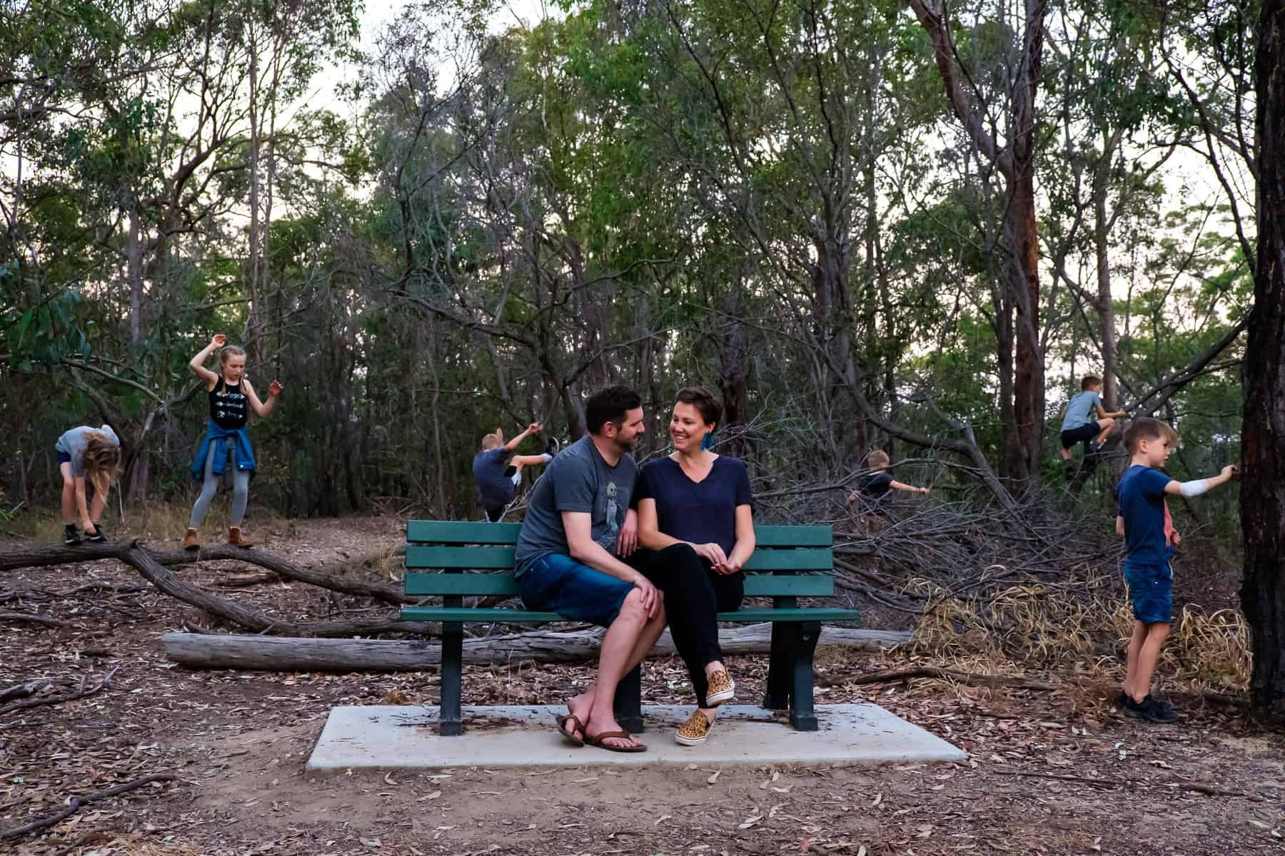 Couple sit on park bench whilst their 6 kids play in the bush around them