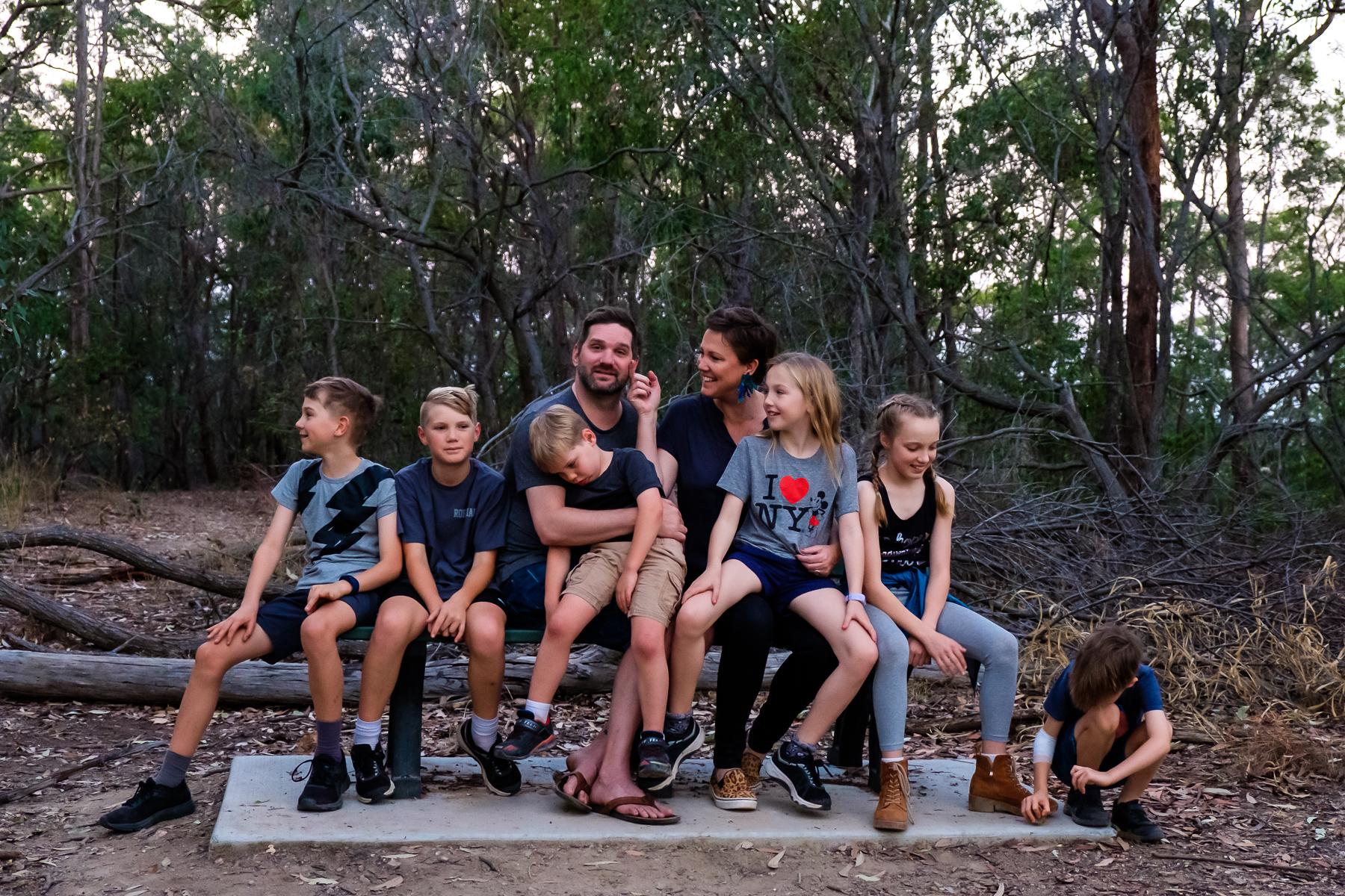 Family with 6 kids sitting on park bench