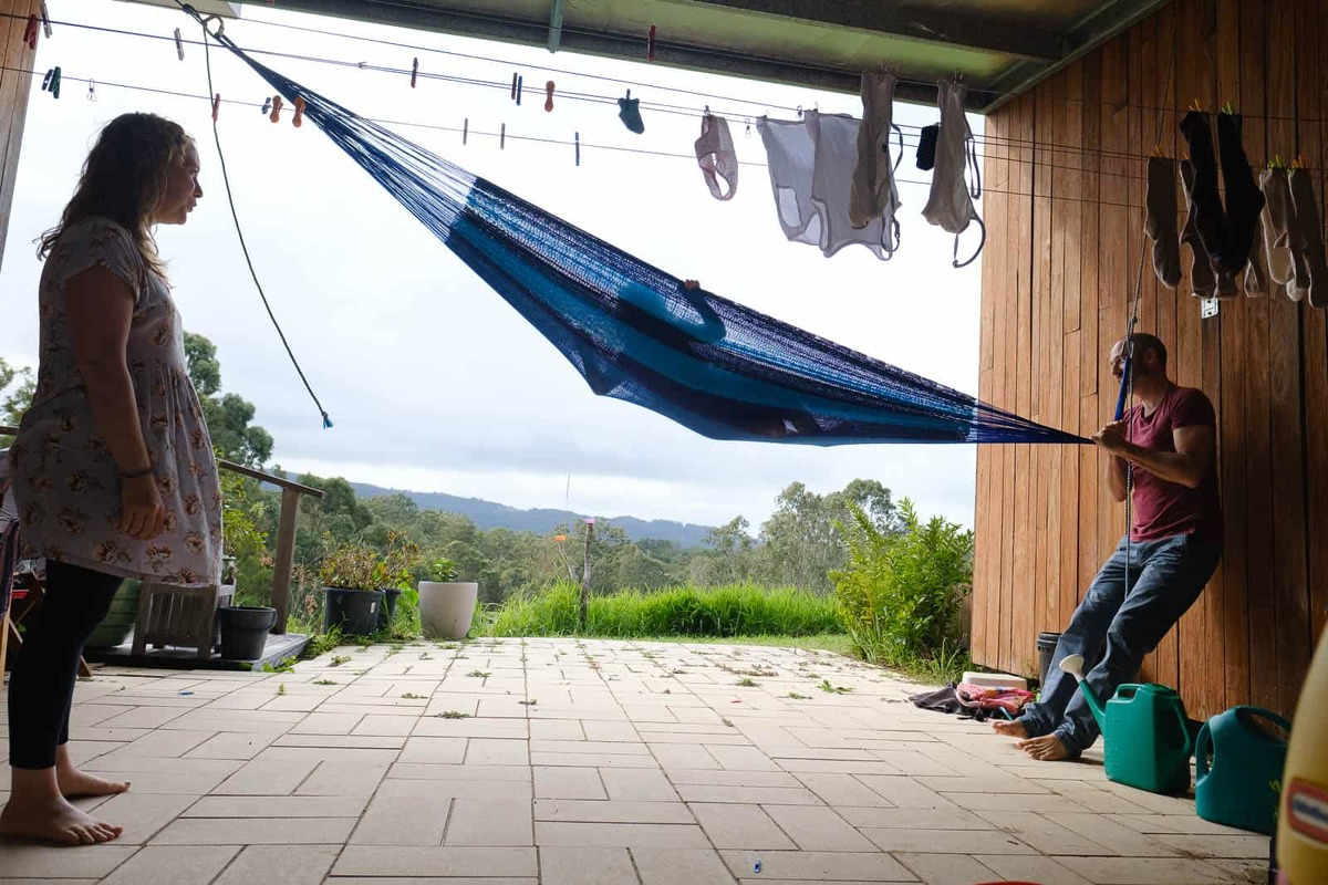 Colour image of Dad swinging daughter up in hammock as mum looks on